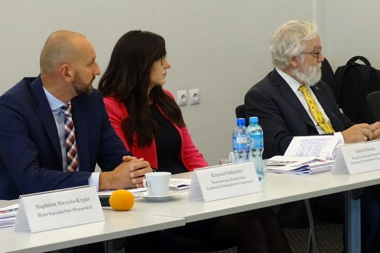 zdjęcie: przy stole siedzą dwaj mężczyźni i jedna kobieta
