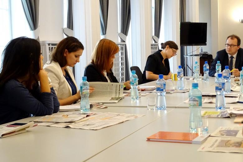zdjęcie: kilkaosób siedzi przy stole konferencyjnym, na którym są rozłożone gazety