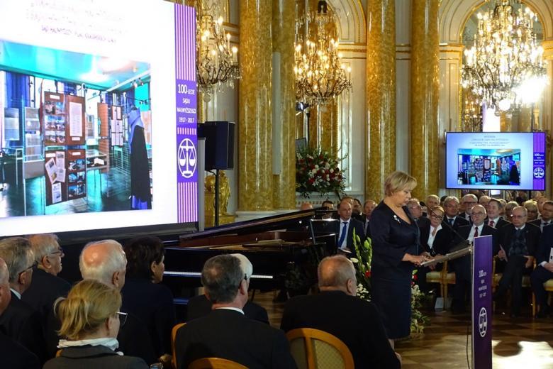 zdjęcie: kilkanaście osób siedzi na sali, kobieta w ciemnej sukience stoi przy mównicy