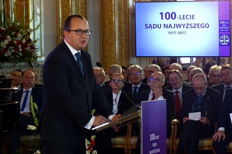 zdjęcie: mężczyzna w garniturze stoi przy mównicy za nim siedzi kilkanaście osób