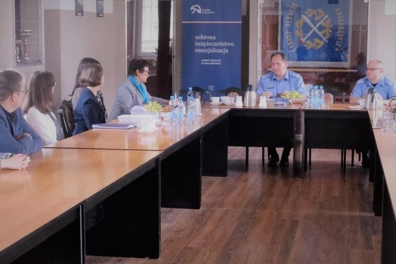 zdjęcie: kilka osób siedzi za stołami, dwaj mężczyźni u szczytu stołu są w mundurach