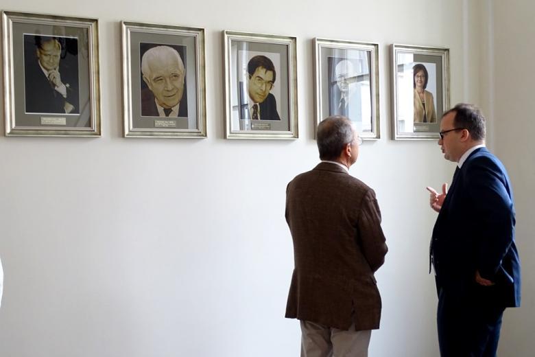 zdjęcie: dwóch mężczyn ogląda portrety wiszące na ścianie
