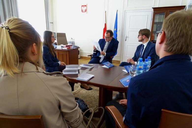 zdjęcie: kilka osó siedzi przy okrągłym stole, mężczyzna w garniturze odczytuje tekst z kartki