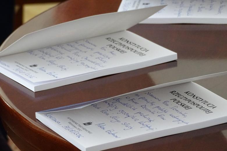 zdjęcie: na stle leżą otwarte konstytucje, widać fragmenty zapisanych odręcznie dedykacji