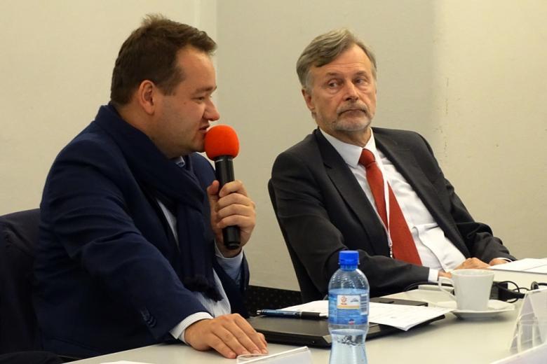 zdjęcie: przy stole siedzą dwaj mężczyźni, jeden z nich mówi do mikrofonu