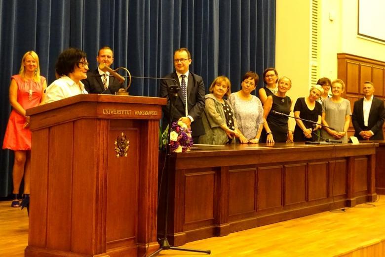 zdjęcie: za mównicą stoi starsza kobieta, obok jest stół prezydialny za którym stoi kilka osób