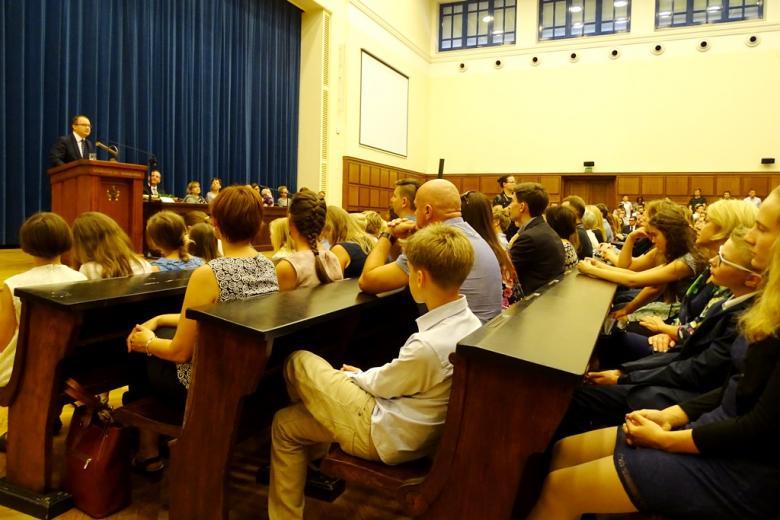 zdjęcie: kilkadziesiąt osób siedzi na auli, w tle widać mównicę i stół prezydialny
