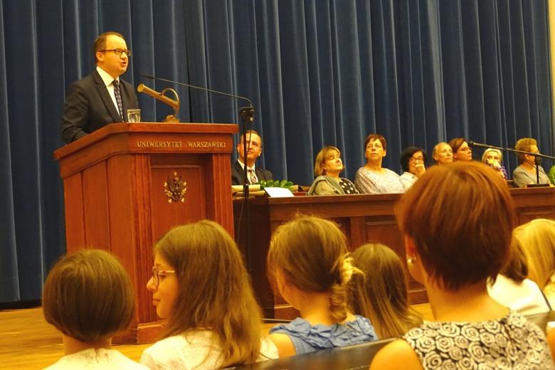 zdjęcie: widać siedzących tyłem ludzi na auli, przed nimi scena, na której za mównicą stoi mężczyzna