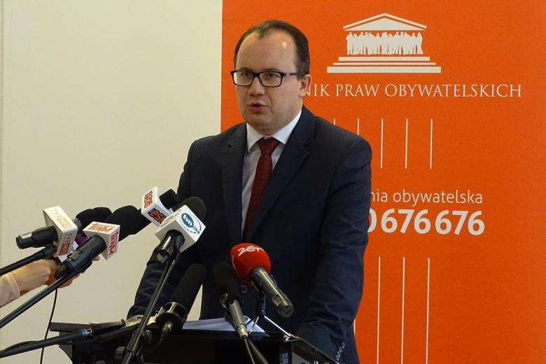 zdjęcie: mężczyzna w garniturze stoi przy mównicy, przed nim stoi kilka mikrofonów