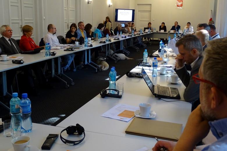 zdjęcie: przy stołach siedzi kilkanaście osób, część osób ma słuchawki służące tłumaczeniom, po środku sali widać leżącego psa przewodnika
