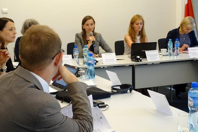 zdjęcie: na pierwszym planie bokiem siedzi mężczyzna w garniturze, patrzy na kobietę która przemawia do mikrofonu
