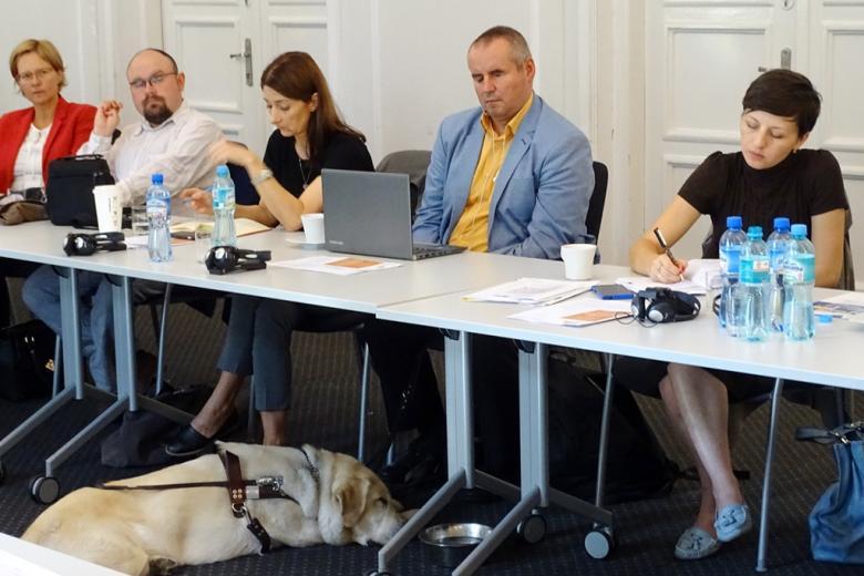 zdjęcie: kilka osób siedzi za stołem, pod stołem widać leżącego psa przewodnika, przy którym stoi miska z wodą