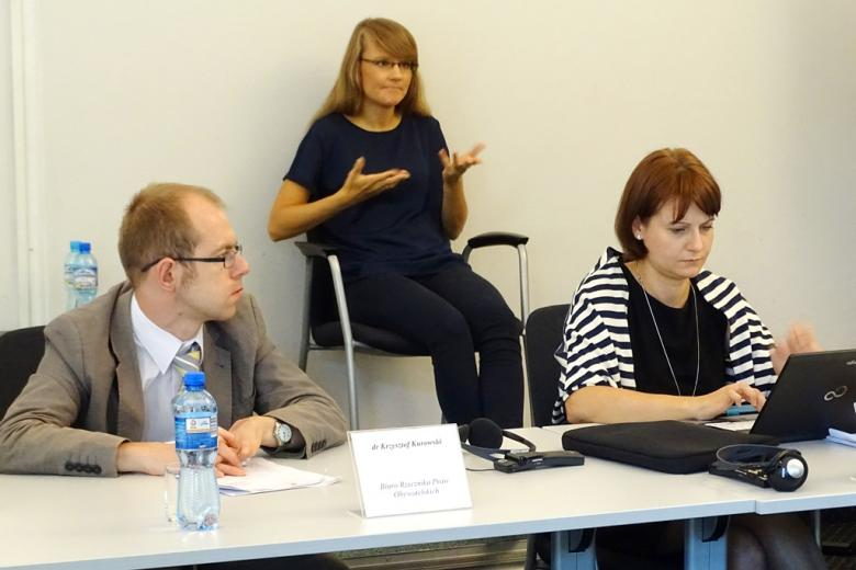 zdjęcie: mężczyzna i kobieta siedzą za stołem, za nimi na podwyższeniu siedzi kobieta, która miga