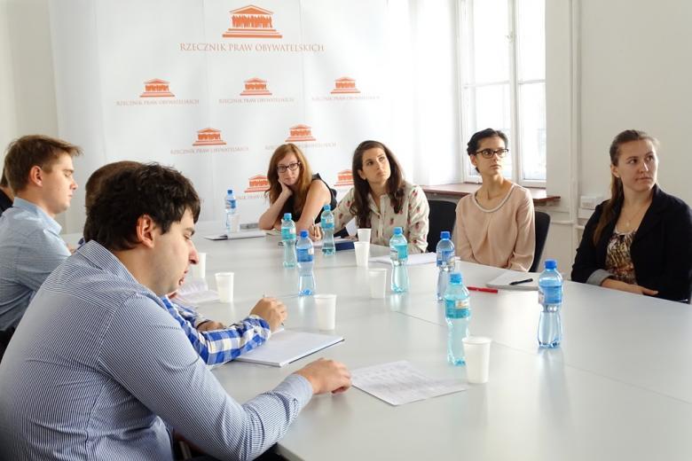 zdjęcie: kilka osób siedzi przy złączonych stołach