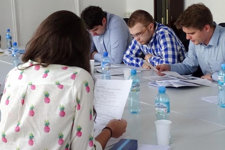 zdjęcie: dziewczyna siedzi tyłem do obiektywu, spogląda na kartkę papieru, naprzeciw niej siedzi trzech mężczyzn