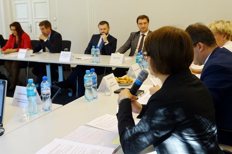 zdjęcie: bokie widać kobietę w krórto obciętych włosach, która mówi do mikrofonu, na wprost obiektywu siedzi trzech mężczyzn
