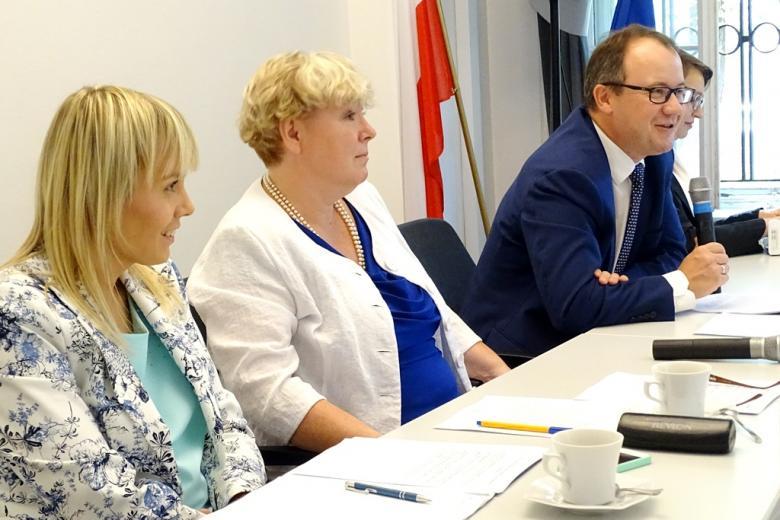 zdjęcie: bokiem siedzą dwie kobiety w jasnych żakietach, obok nich mężczyzna mówiący do mikrofonu