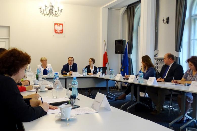 """zdjęcie: za stołami ustawionymi w """"podkowę"""" siedzi kilkanaście osób, mężczyzna za stołem prezydialnym przemawia do mikrofonu"""