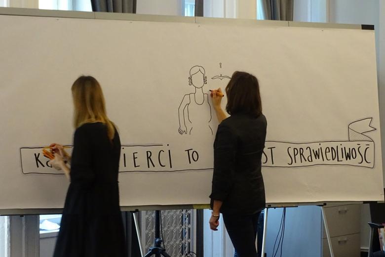 zdjęcie: przy ogromnej tablicy stoją dwie kobiety i rysują