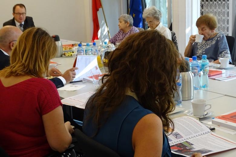 zdjęcie: kilka osób siedzi przy stołach i przeglada broszury informacyjne