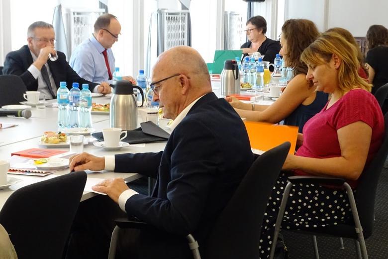zdjęcie: kilka osób siedzi przy stole i przegląda broszury informacyjne