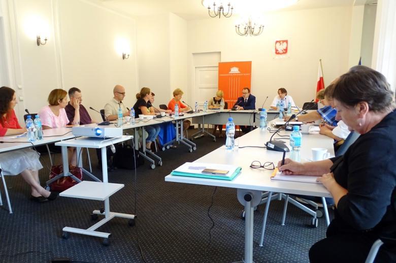 zdjęcie: za ustawionymi w krształcie litery U stołami siedzi kilkanaście osób