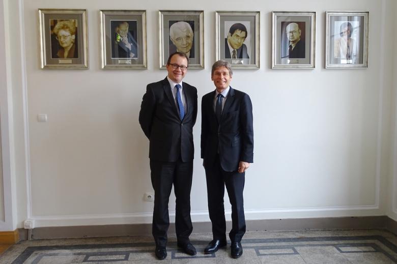 zdjęcie: dwóch mężczyzn w garniturach stoi na tle wiszących na wysokości ich głów portretów