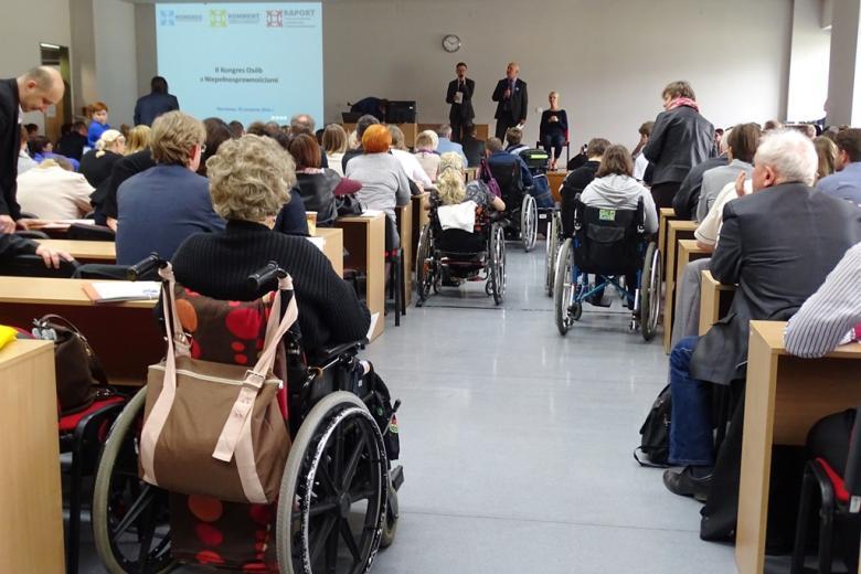 zdjęcie: tyłem ukazana siedząca publiczność, w tym osoby na wózkach, na podwyższniu stoją dwie osoby