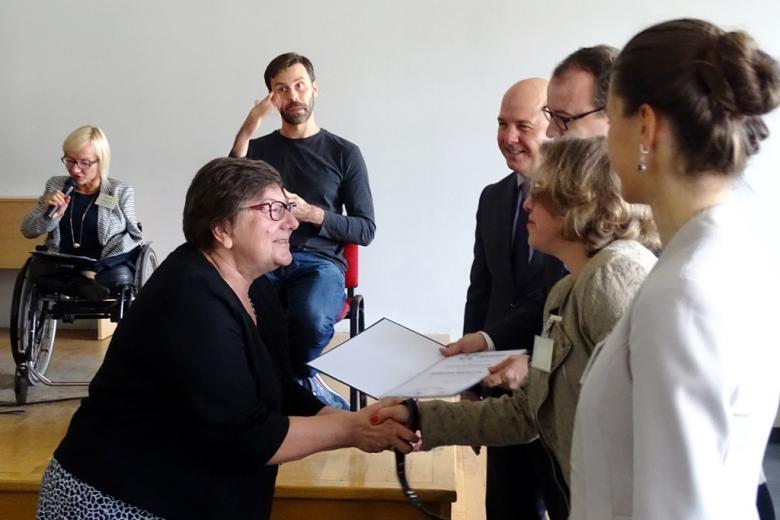 zdjęcie: kobieta odbiera dyplom od kilku osób, które stoją po prawej stronie