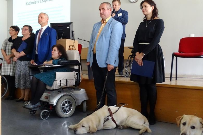 zdjęcie: kilka osób stoi, na pierwszym planie jest mężczyna z psem przewodnikiem, obok niego siedzi kobieta na wózku