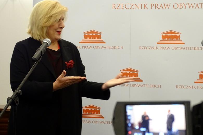 zdjęcie: kobieta w czranym ubrani stoi i rękami wskazuje w prawą stronę