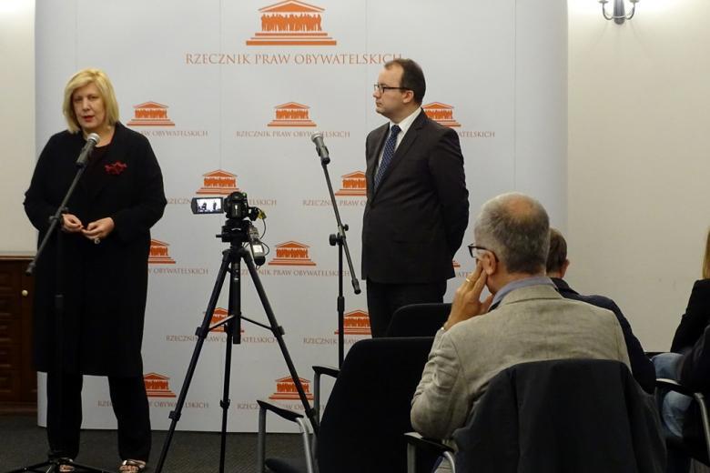 zdjęcie: na pierwszm planie widać kamerę i siedzące osoby, przed nimi na tle biało-pomarańczowej ścianki stoją kobieta i mężczyzna