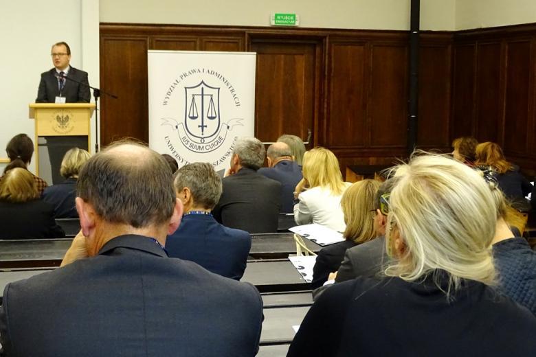 zdjęcie: mężczyznz w tle stoi za mównicą przed nim na auli wykładowej siedzi kilkanaście osób