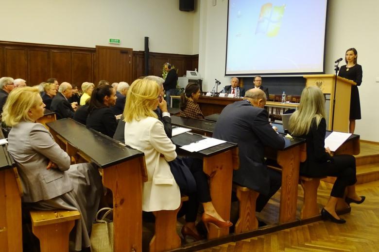 zdjęcie: kobieta stoi przy mówcicy przed nią na auli siedzi kilkadziesiąt osób