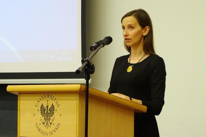 zdjęcie: kobieta w czarnej sukience stoi przy mównicy