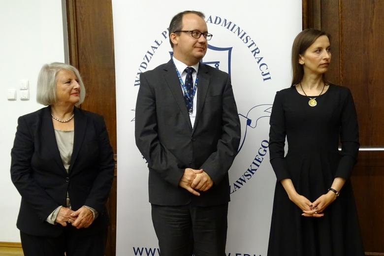 zdjęcie: dwie kobiety i mężczyzna pomiedzy nimi stoją i patrzą w lewą stronę
