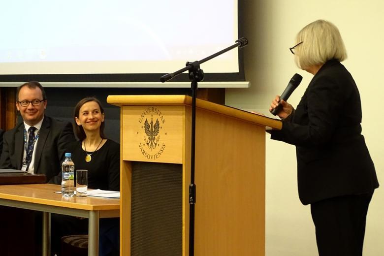 zdkęcie: kobieta w czernym stroju stoi przy mównicy, jest zwrócona w prawą stronę gdzie za stołem siedzi kobieta i mężczyzna