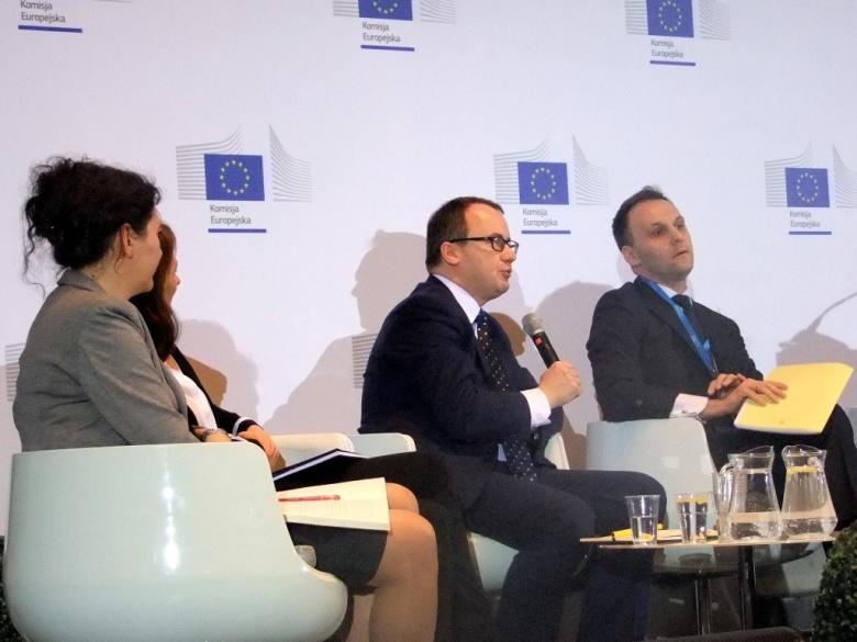 zdjęcie: dwie kobiety i dwóch mężczyzn siedzi na białych fotelach przy małym szklanym stoliku, jeden z mężczyzn mówi do mikrofonu