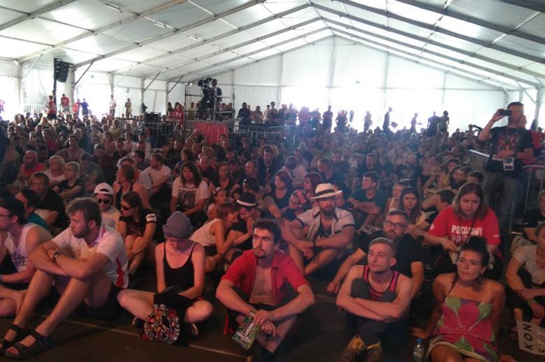 zdjęcie: w ogromnym namiocie na podłodze siedzi kilkadziesiąt osób