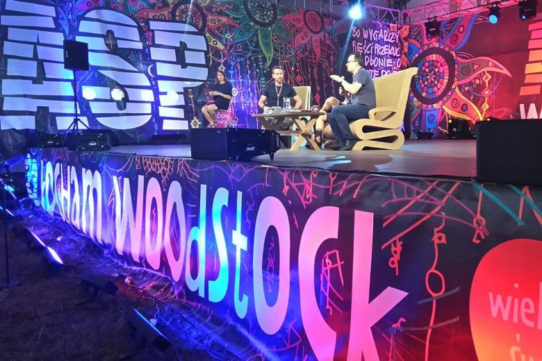 zdjęcie: na scenie siedzą trzej mężczyźni ubrani na sportowo
