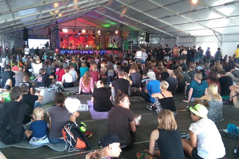 zdjęcie: na podłodzie siedzi kilkadziesiąt osób przed niki stoi scena, na której siedzą trzej mężczyźni