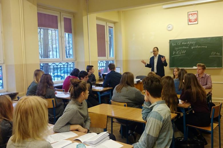 zdjęcie: mężczyzna chodzi po sali, przy stołach siedzą młodzi ludzie