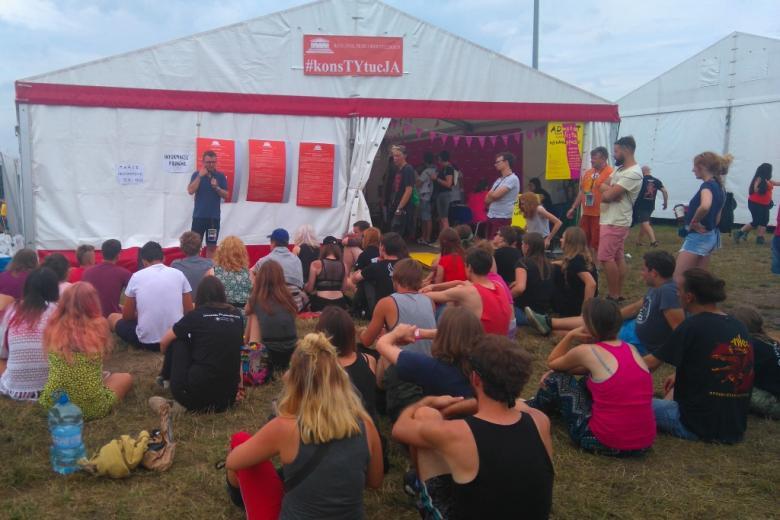 zdjęcie: przed namiotem na trawie siedzi kilkanaście osób przed nimi stoi mężczyna