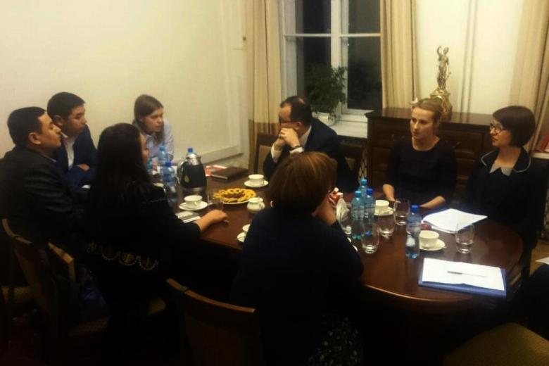 zdjęcie: kilka osób siedzi przy brązowym stole