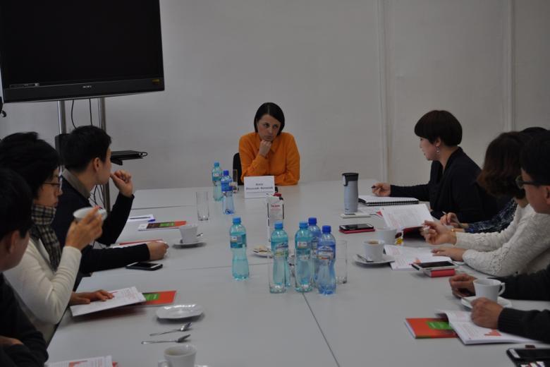 zdjęcie: kilka osób siedzi przy białym stole, na wprost obiektywu siedzi kobieta w krótkich włosach w pomarańczowej koszuli