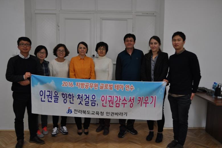 zdjęcie: kilka osób stoi i trzyma baner z napisem po koreańsku
