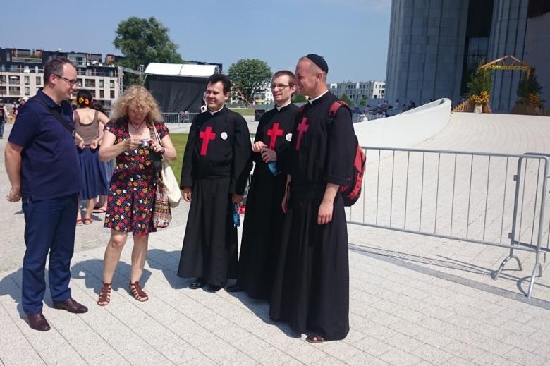Zdjęcie: grupa ludzi w tym zakonnicy w sutannach z czerwonymi krzyżami