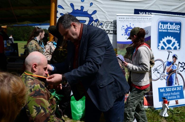 Zdjęcie: mężczyzna zawiesza medal na szyi zawodnika na wózku