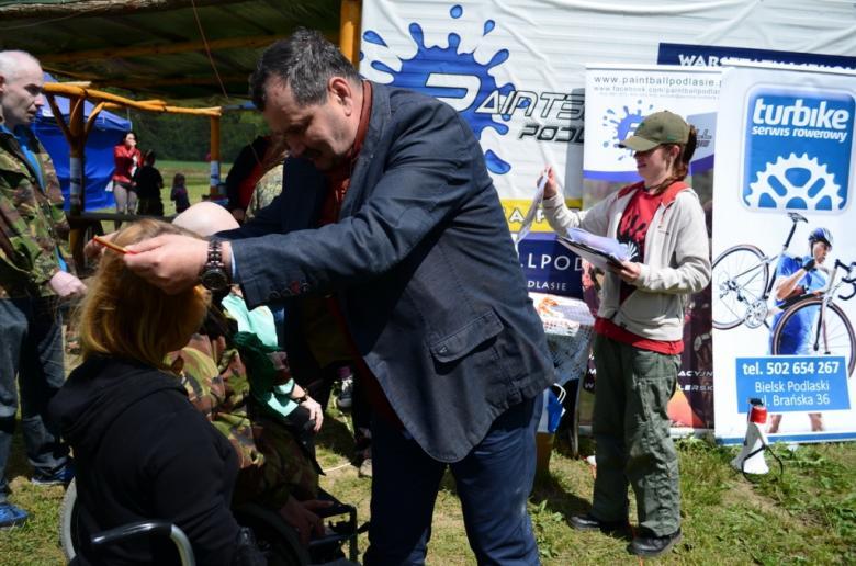 zdjęcie: mężczyzna zawiesza medal na szyi kobiety na wózku inwalidzkim