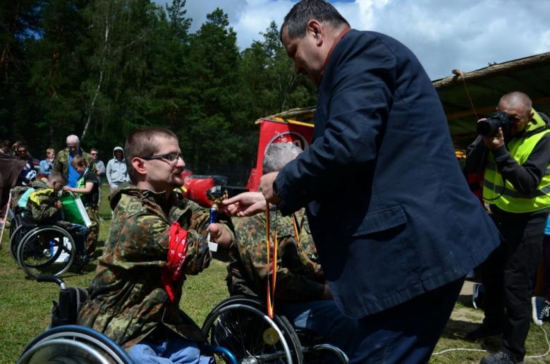 zdjęcie: mężczyzna wręcza mężczyźnie na wózku inwalidzkim złoty puchar